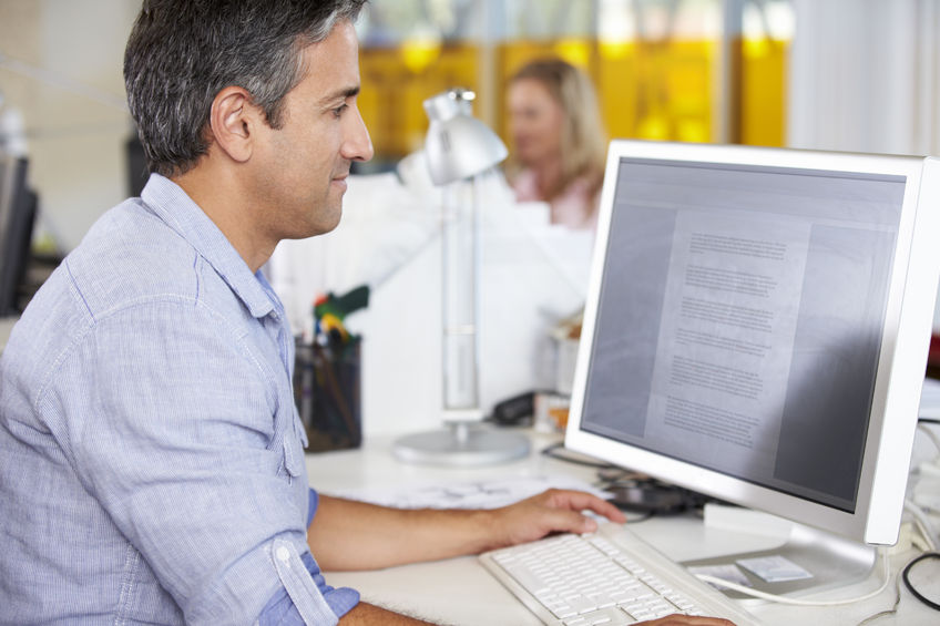 23128595 - man working at desk in busy creative office